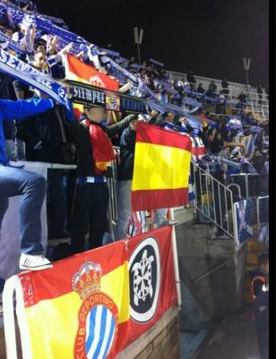 Un membres de les joventuts de PxC animant l'Espanyol sobre una bandera de la Casa Pound.